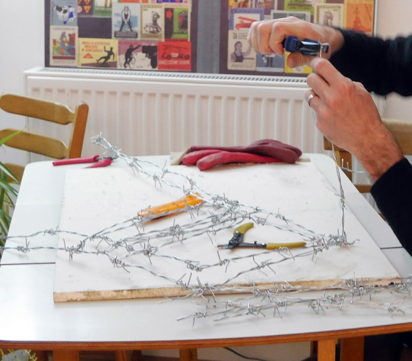 artist's hands working with barbed wire