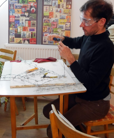 artist working with barbed wire